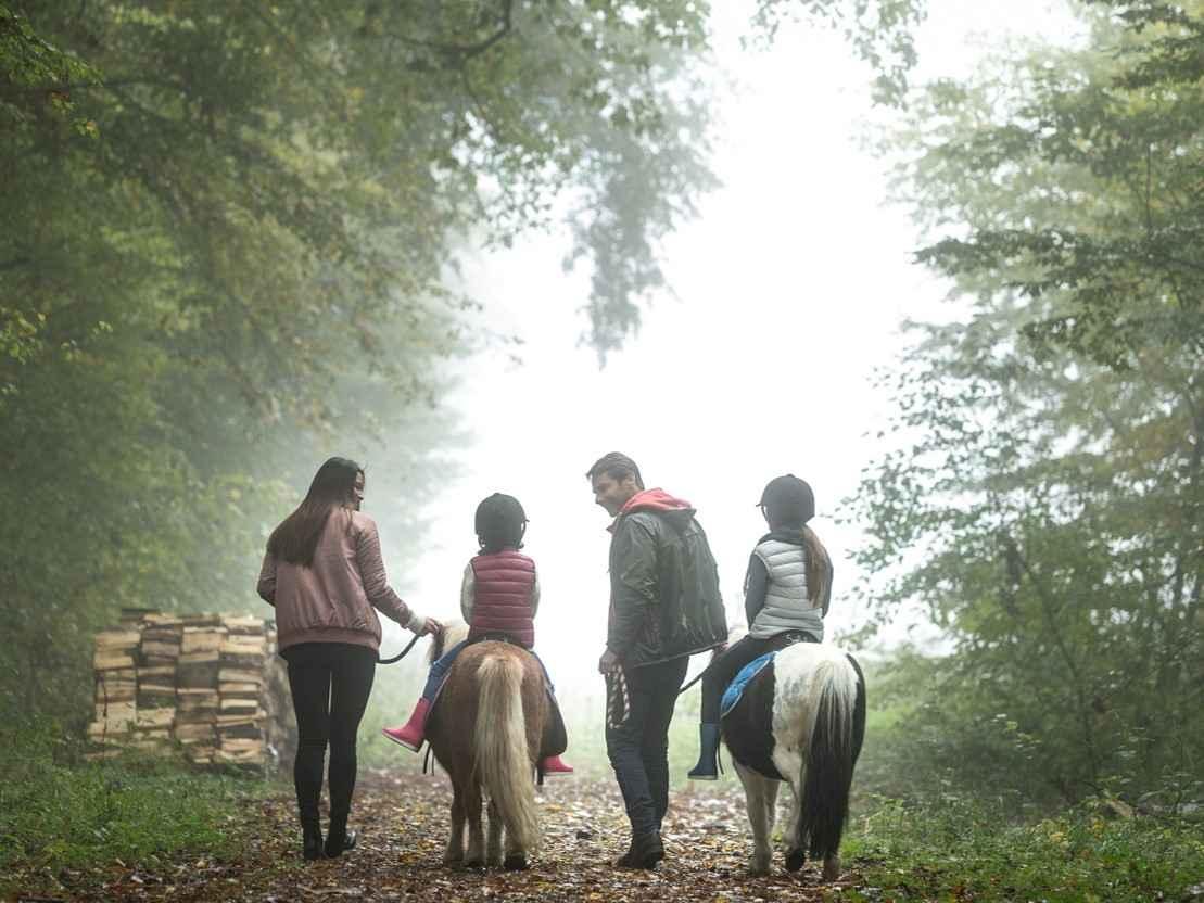 Photo 3 - Famille poney de dos © Cécil Mathieu - Center Parcs domaine des Bois-Francs